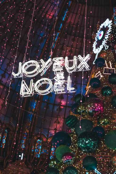 joyeux noel neon signage hanging beside christmas tree